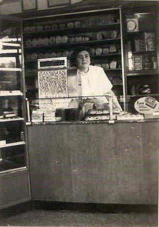 Moeder Jetje Verdooner-de Lara achter haar toonbank, altijd even keurig gekleed en klantvriendelijk. De foto is afkomstig uit het fotoarchief van David Verdooner. Alle rechten voorbehouden