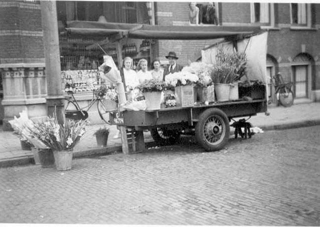 Zomer 1948: opa Meijer met zijn bloemenstal. Bij hem staan beide dochters en de schoondochter van de filiaalchef de Lang. Hij en zijn echtgenote overzien, boven uit het raam hangend, de hele scene. (Met dank aan mevrouw Groot) Alle rechten voorbehouden