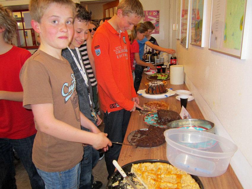 Jorn, met oranje shirt, aan het taart snijden. Alle rechten voorbehouden